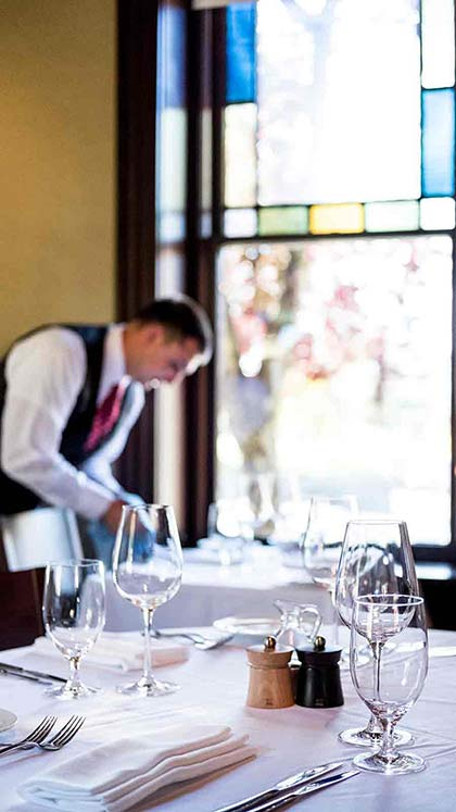 Server preparing a table in the dining room of the Gatehouse Restaurant on the campus of the CIA at Greystone in St. Helena.