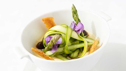 An asparagus salad tops a savory egg custard with chicken confit, mushrooms, and black garlic, served at Gatehouse Restaurant at the CIA at Greystone in St. Helena, CA.